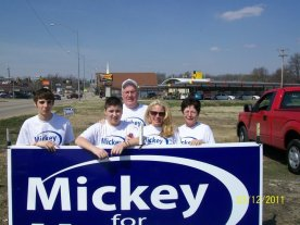 Mickey with family putting up signs for the upcoming election.